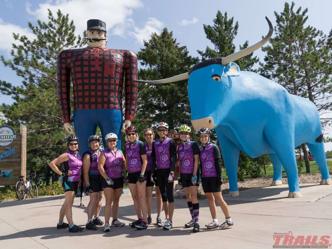 Cyclists pose for a shot with Paul and Babe after making it all the way to Bemidji on the Paul Bunyan Trail