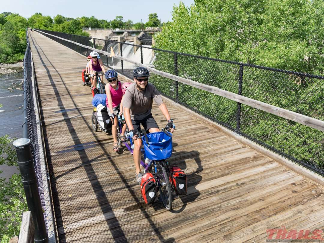 A family of cross-country bikepackers crosses the Blanchard Dam bridge on the Soo Line Trail