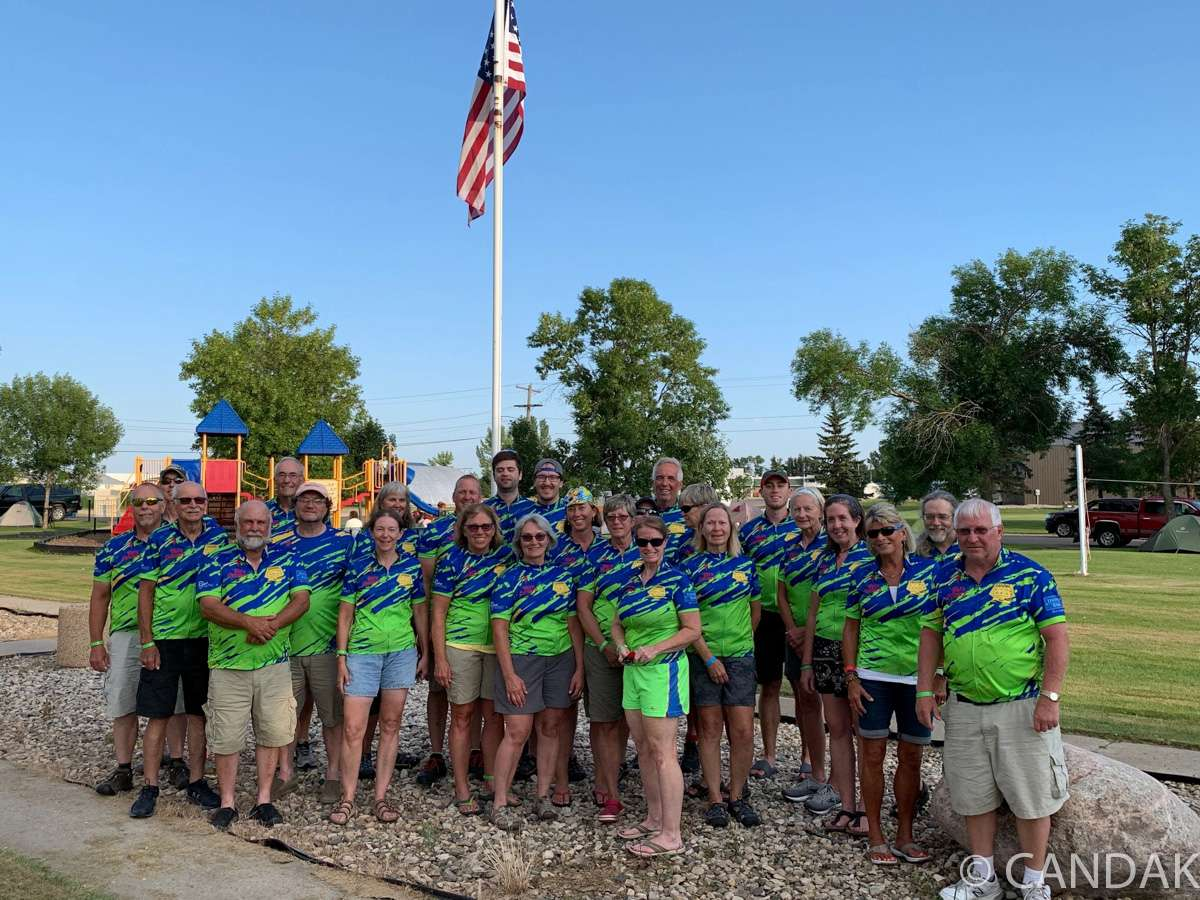 A group of bicyclists is gathered in front of an American flag