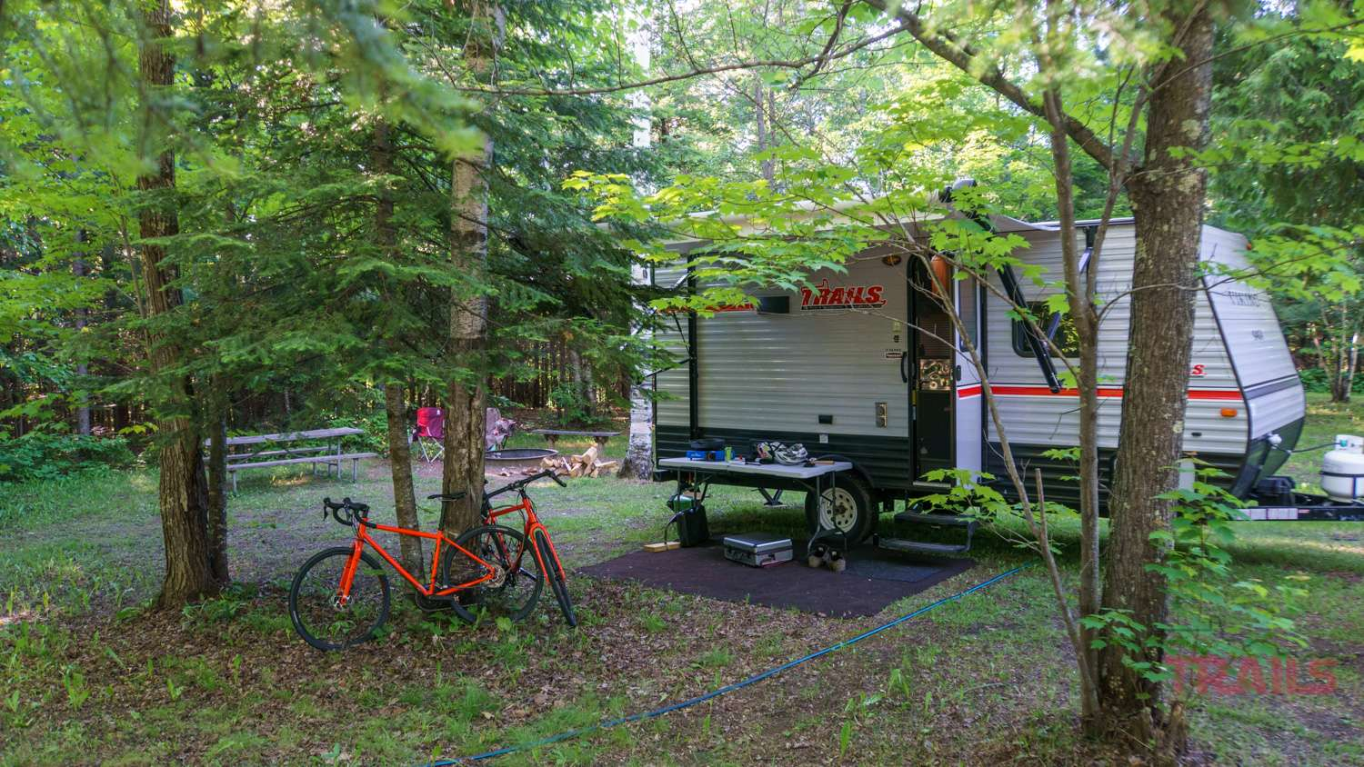 Camping trailer in a wooded campground