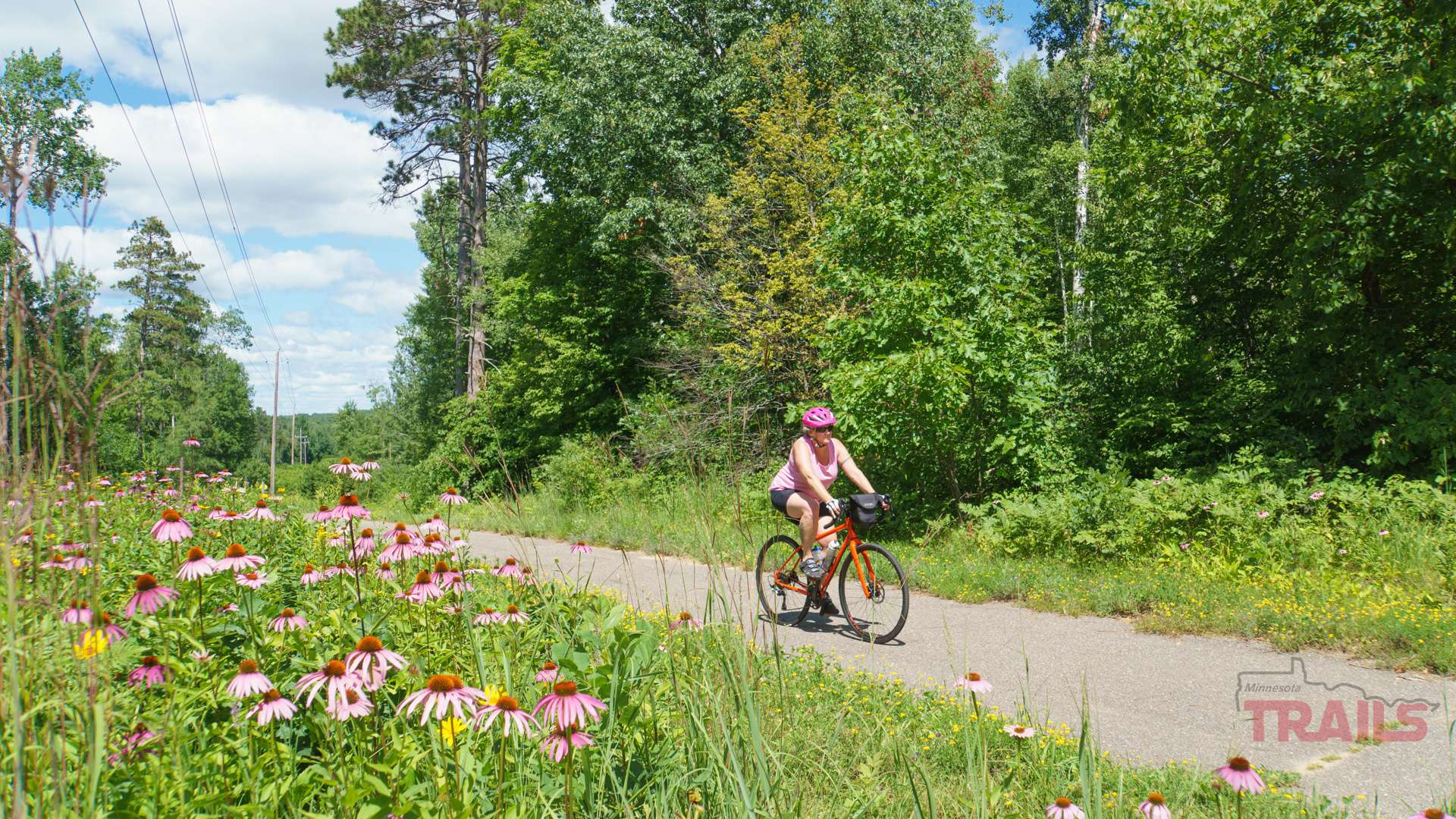 A woman rides a bike on a trail lined with flowers