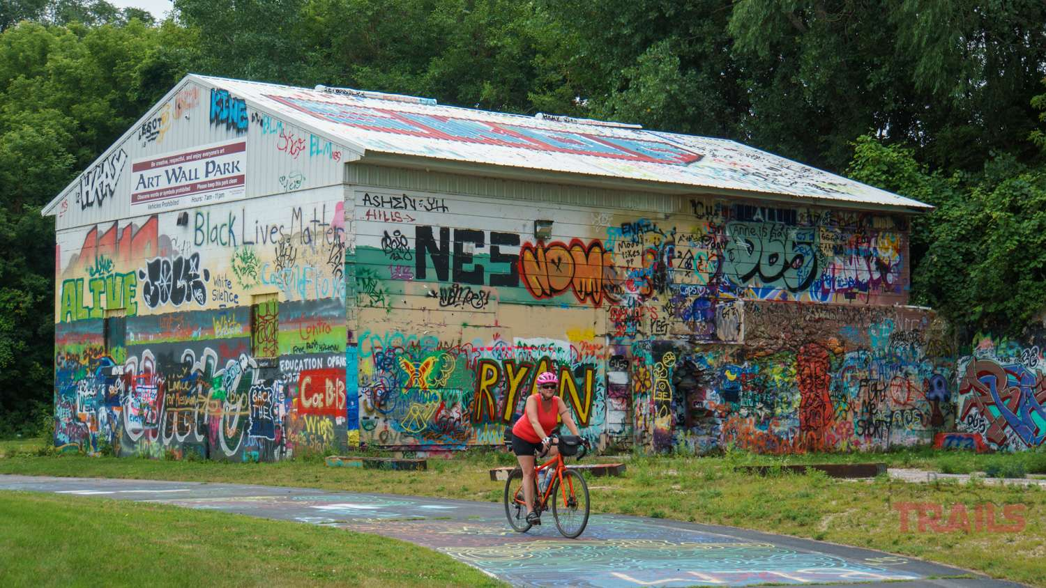 A woman rides a bike in front of a building covered in graffiti