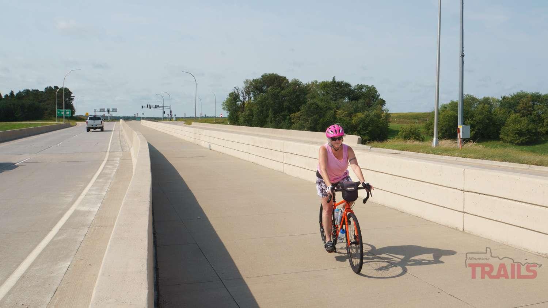 A woman rides a bike on a concrete path