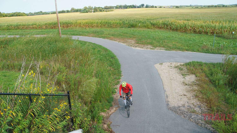 A man rides a bike on a paved path