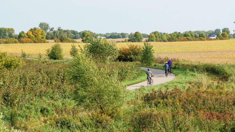 Three people bike on a trail through farm fields