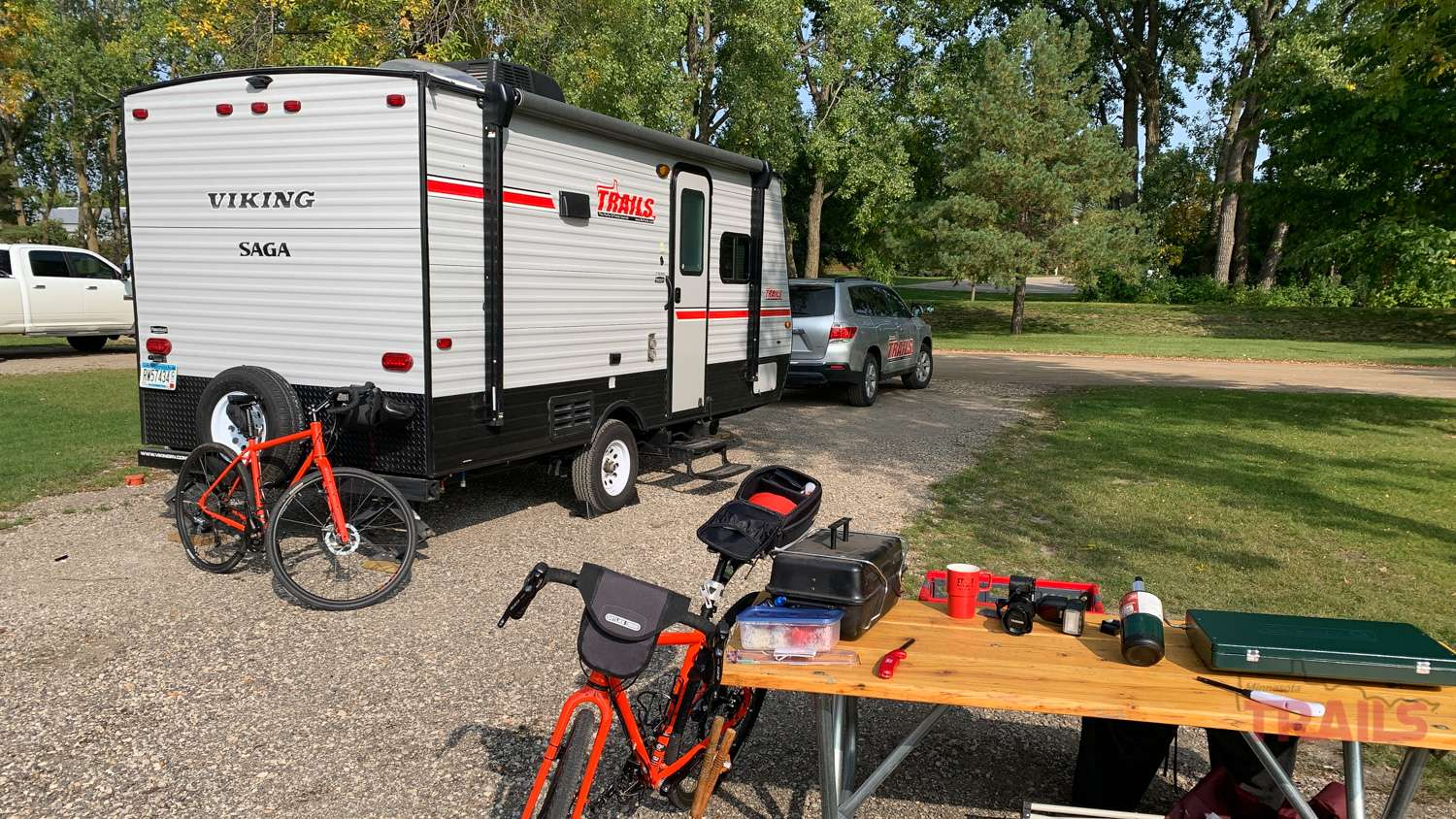 A travel trailer and vehicle in a campsite