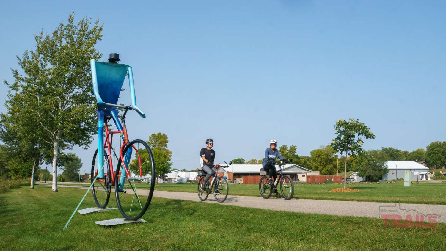 Two people bike by a sculpture of a bicyclist