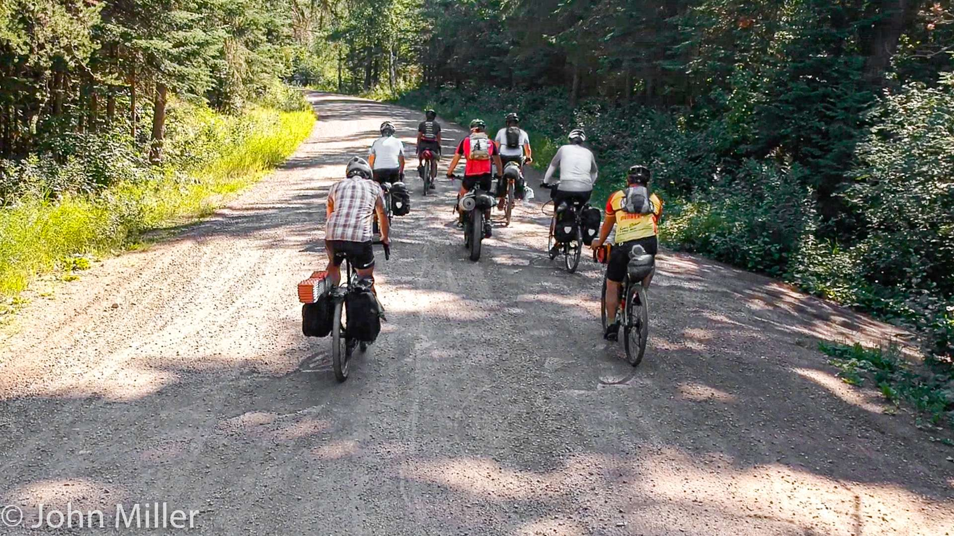 A group of seven cyclists on a gravel road