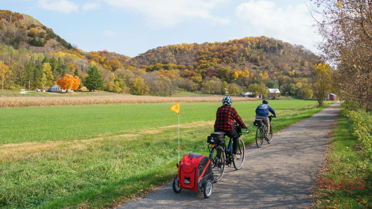 Two people ride bikes on a trail