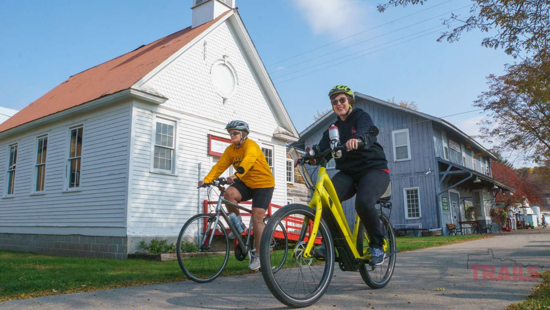 Two women ride bikes on a trail