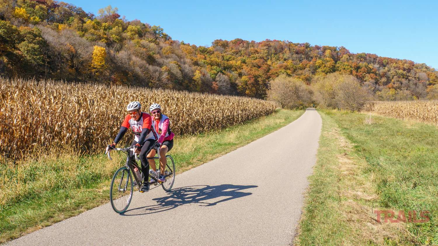 A man and woman ride a tandem bicycle on a trail