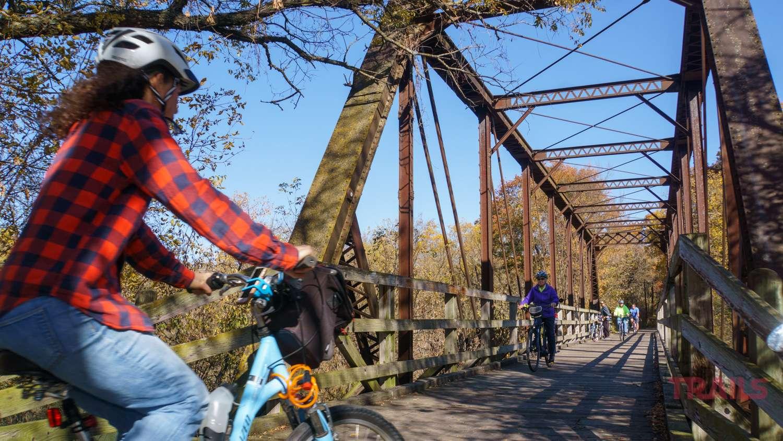 Bicycle riders cross a bridge