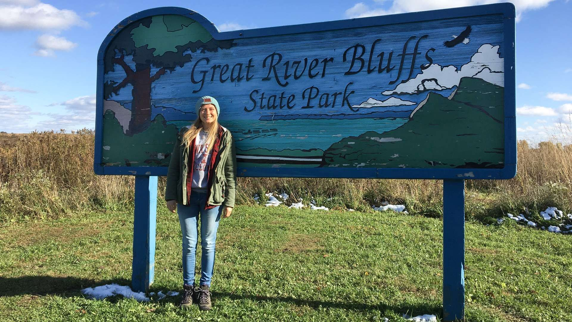 A woman poses in front of the sign for Great River Bluff State Park