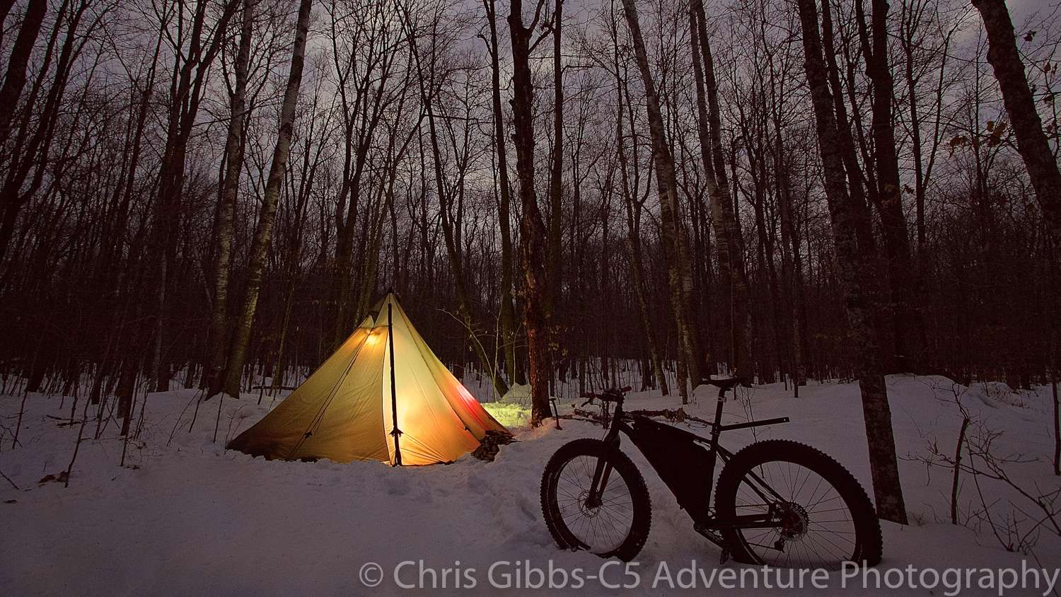 A tent glows with lights on a winter night
