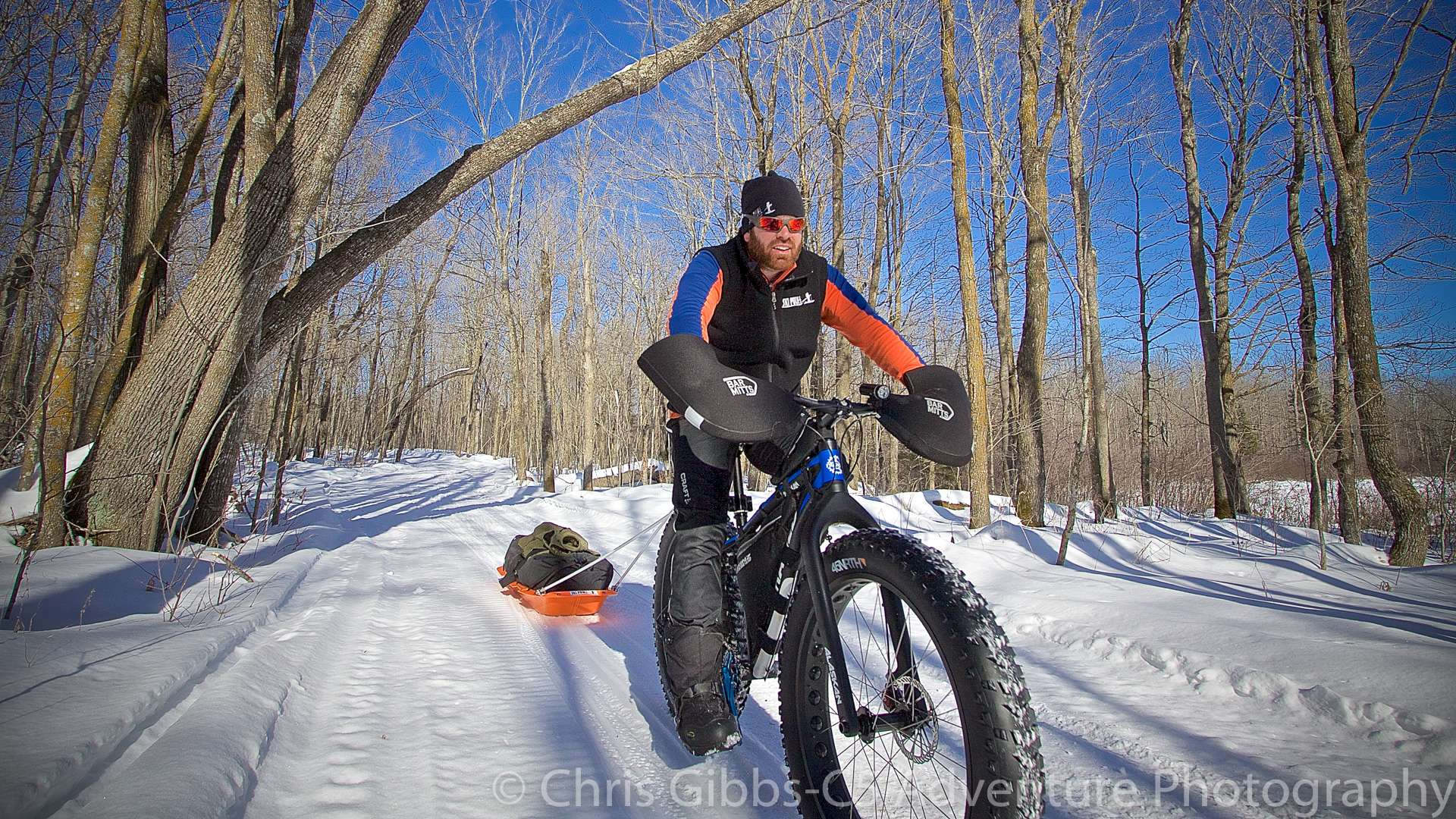 A man pulls a sled with a fatbike in the winter