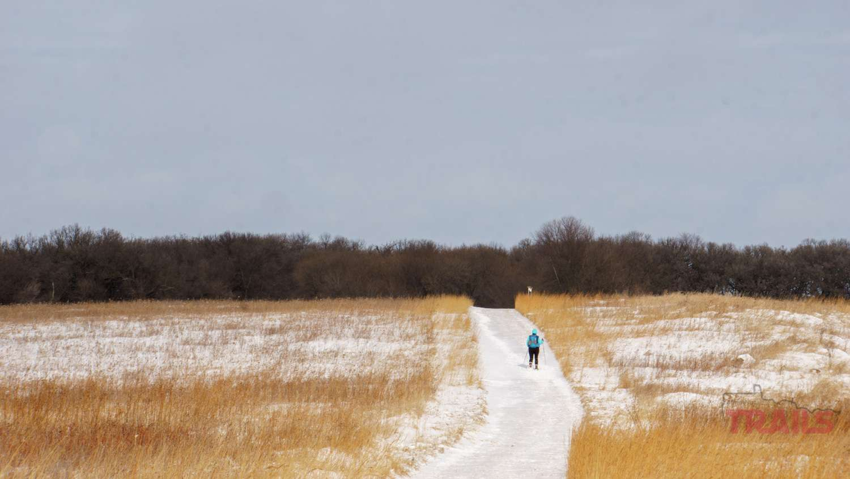A woman walks across the prairie on a snowy trail
