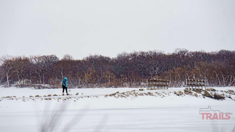A woman walks across a landbridge in a lake in the winter