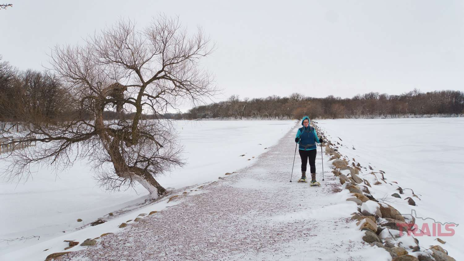 A woman walks on a trail across a lake on snowshoes