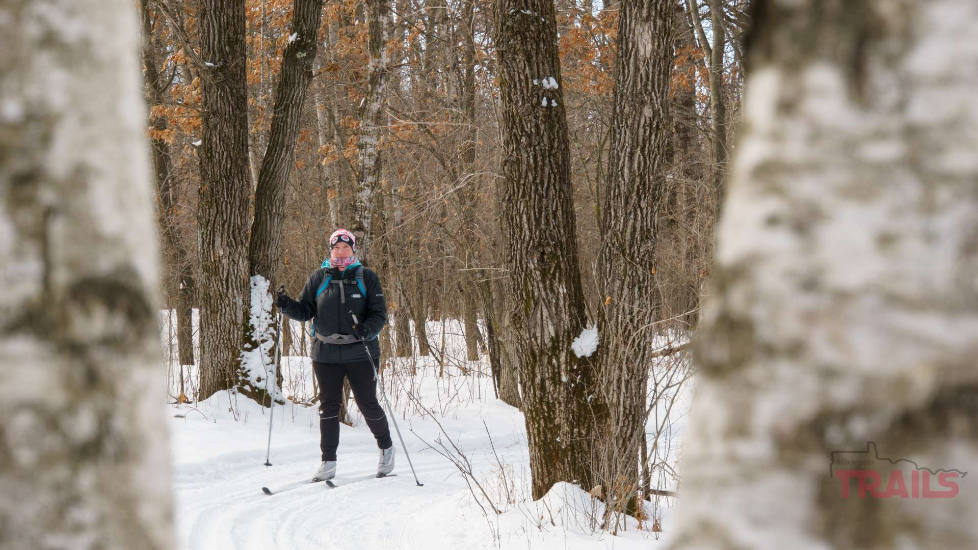 A woman skis through a forest