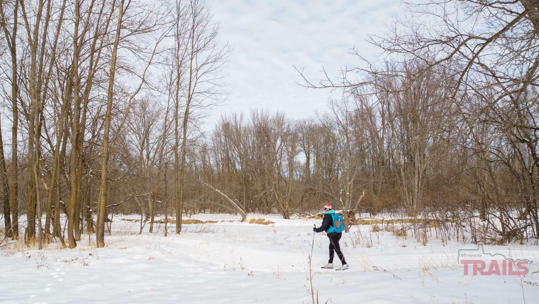 A woman skis along a river