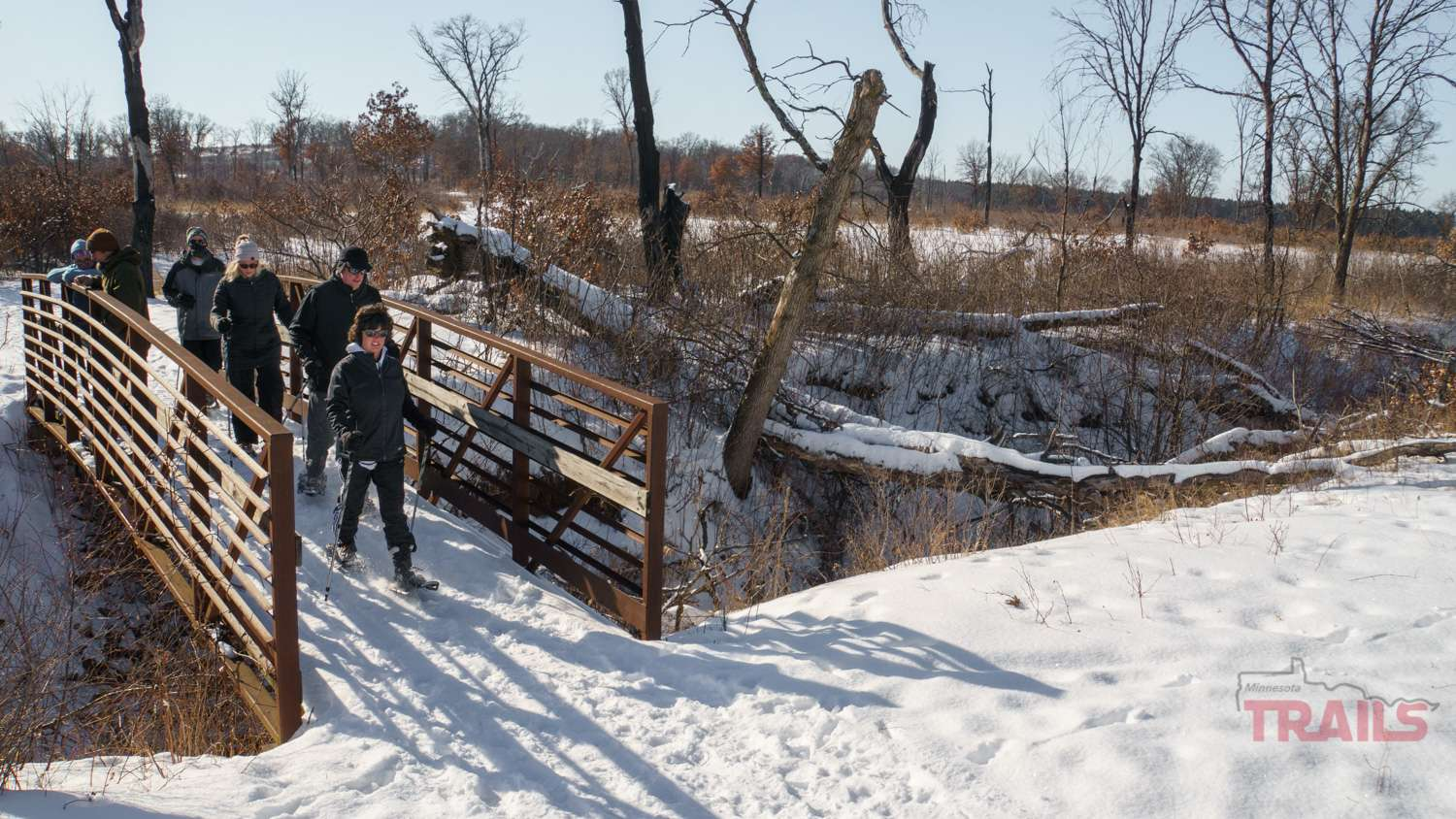 A group of six hikers on a bridge in the winter