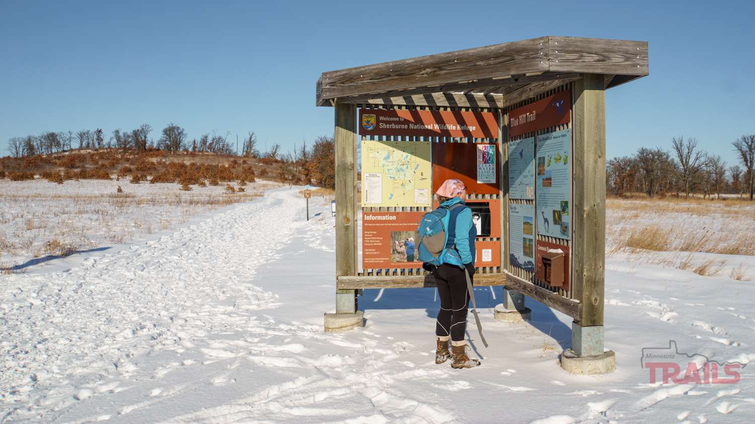 A woman studies an outdoor interpretive kiosk in the winter