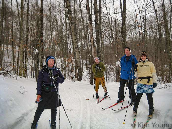 A group of skiers pose for a photo in a forest