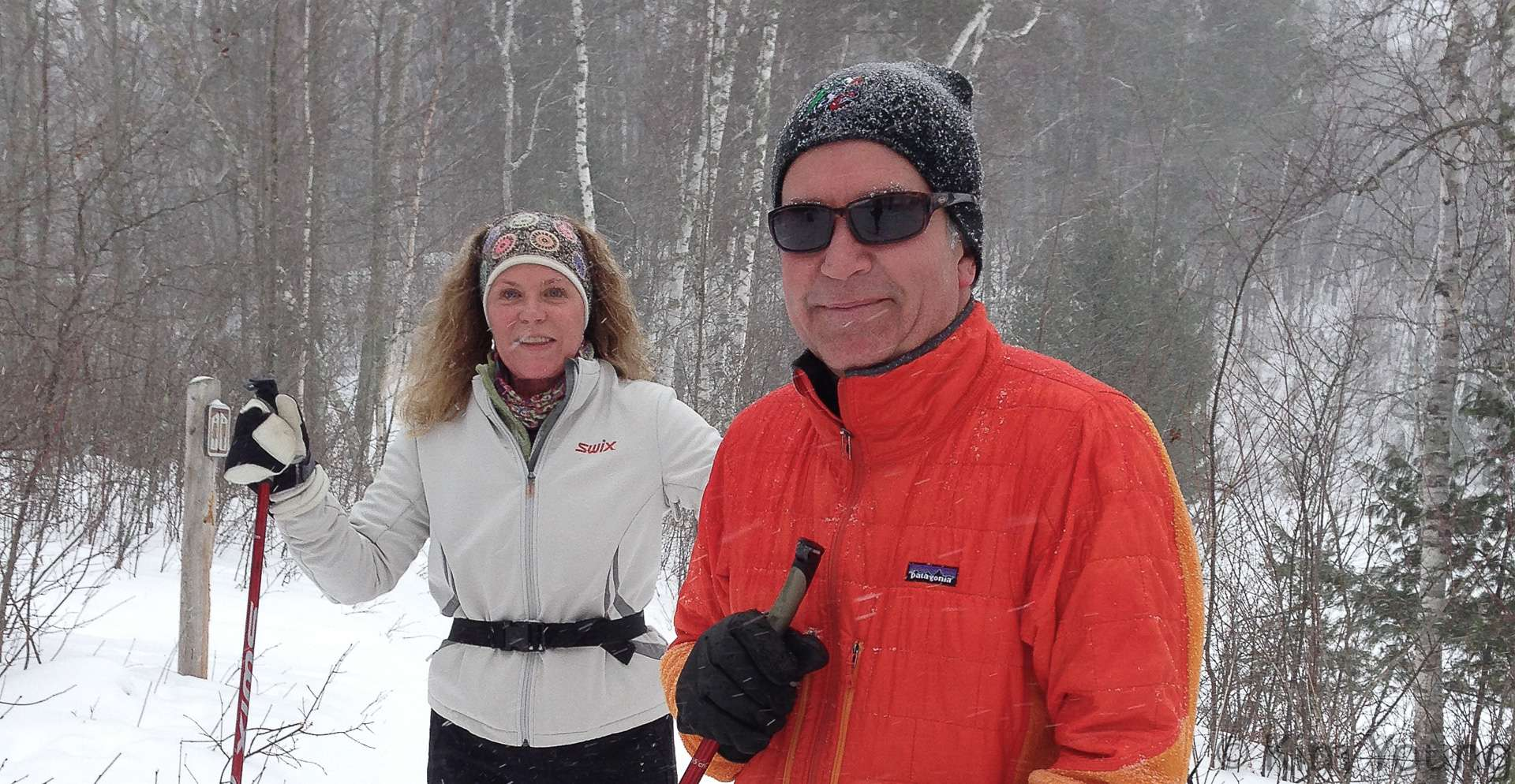 A man and woman on skis pose for a photo