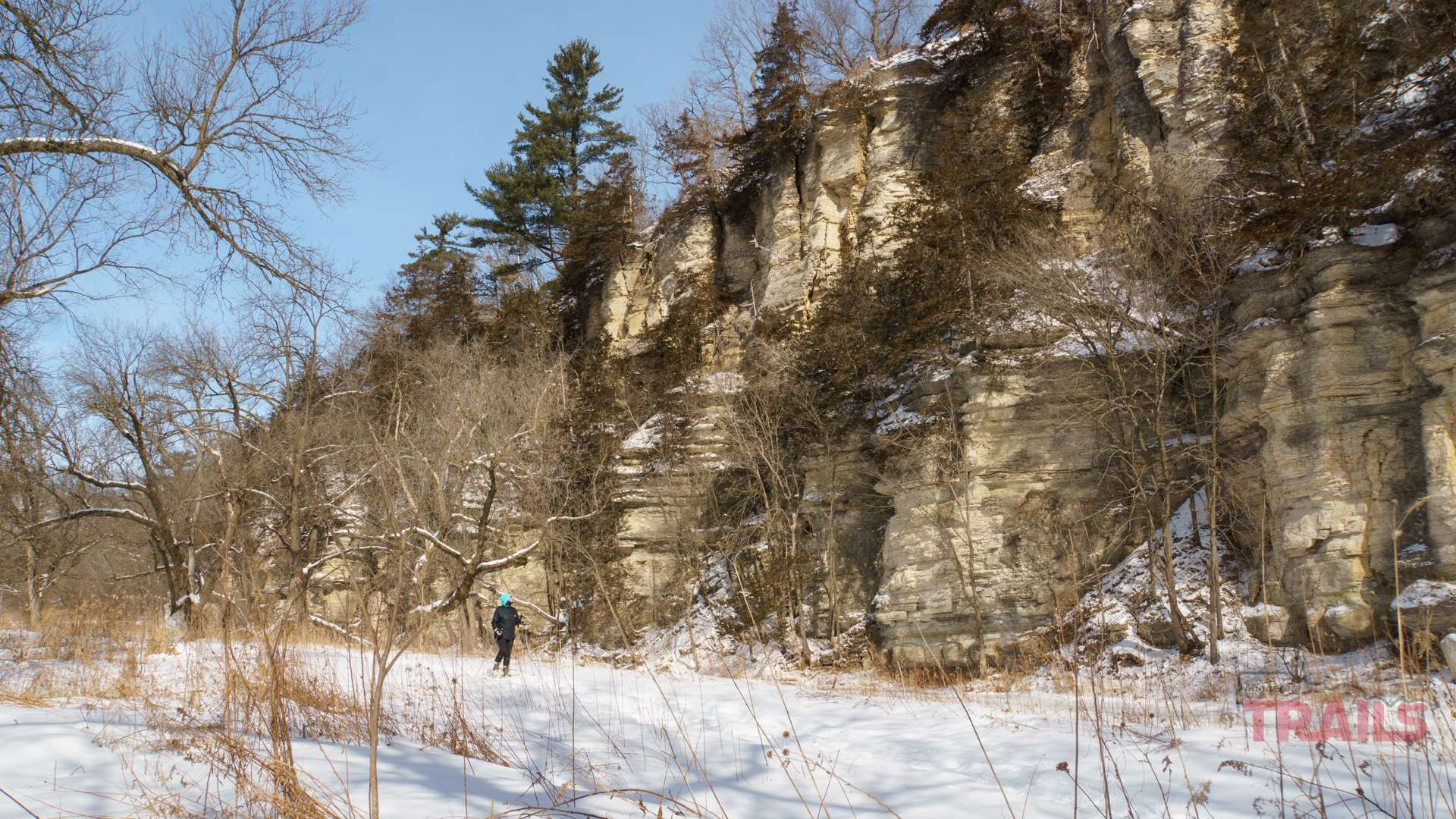 A woman on snowshoes stops to look at a bluffy ridge