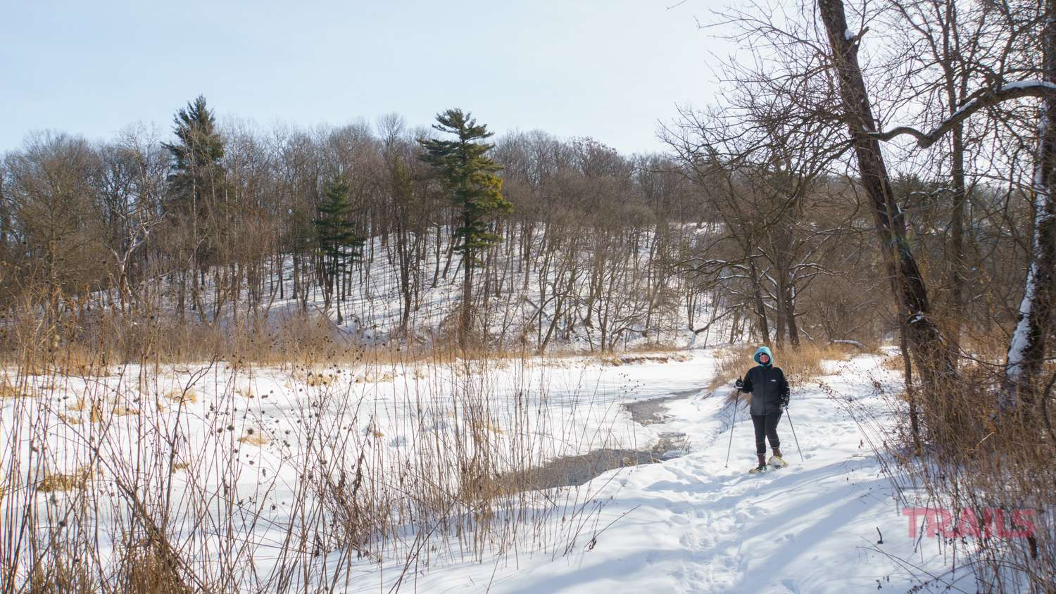 A woman on snowshoes walks along a mostly frozen river