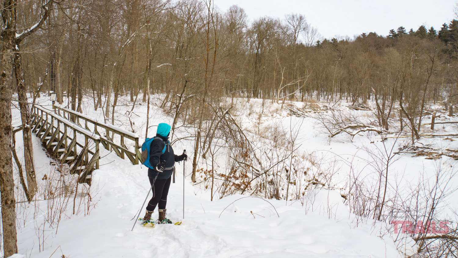 A woman on snowshoes crosses a bridge on the winter