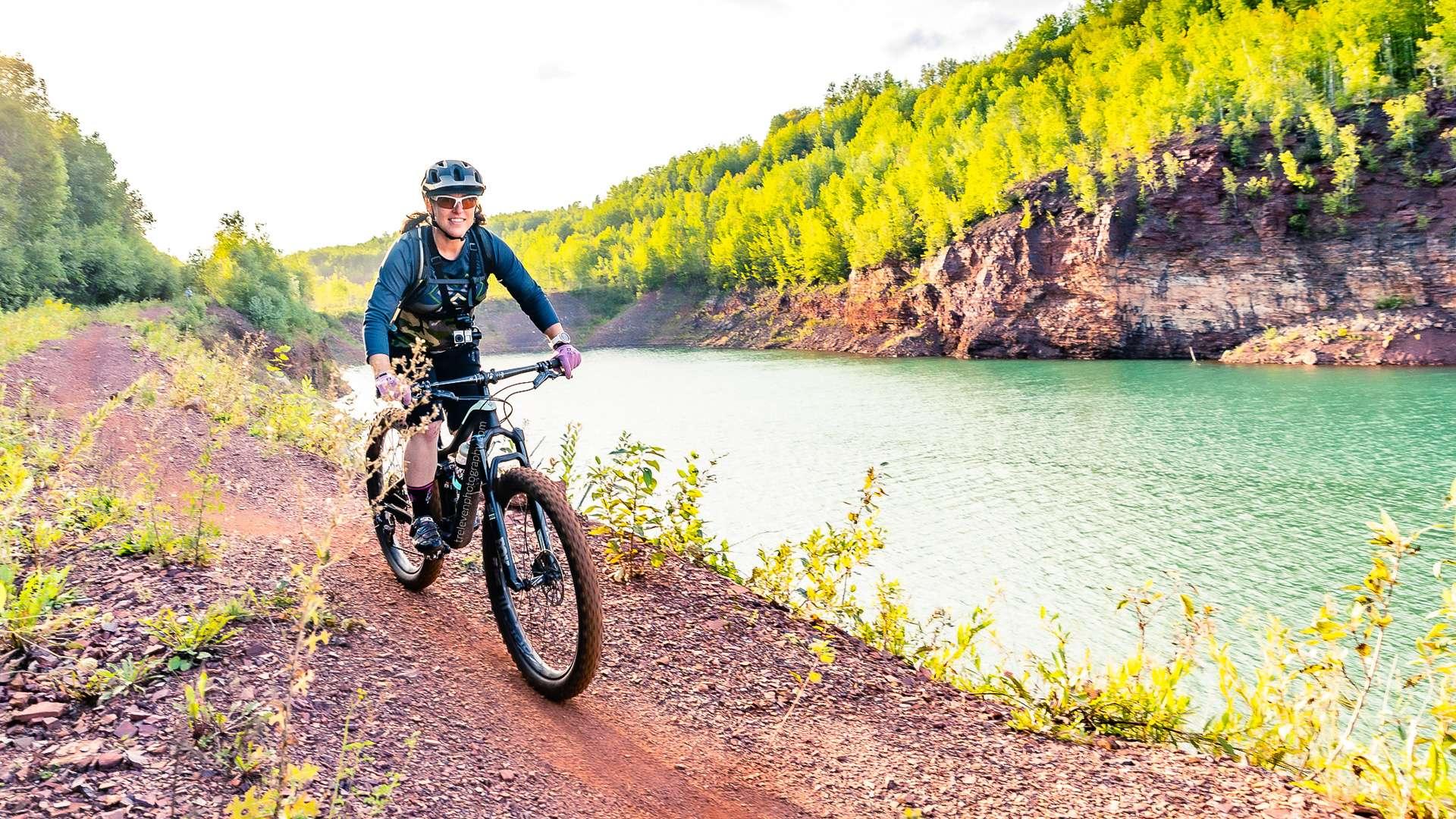 A woman rides her mountain bike along a lake