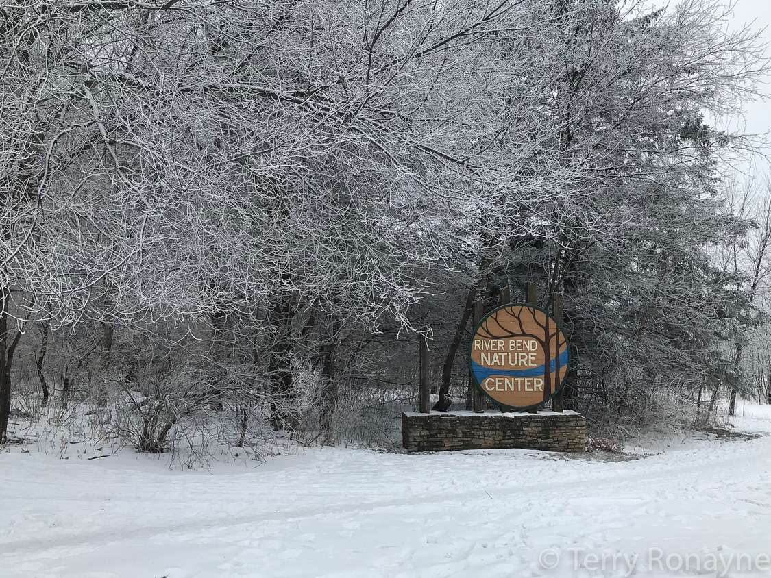 Sign for the River Bend Nature Center in front of frosty trees
