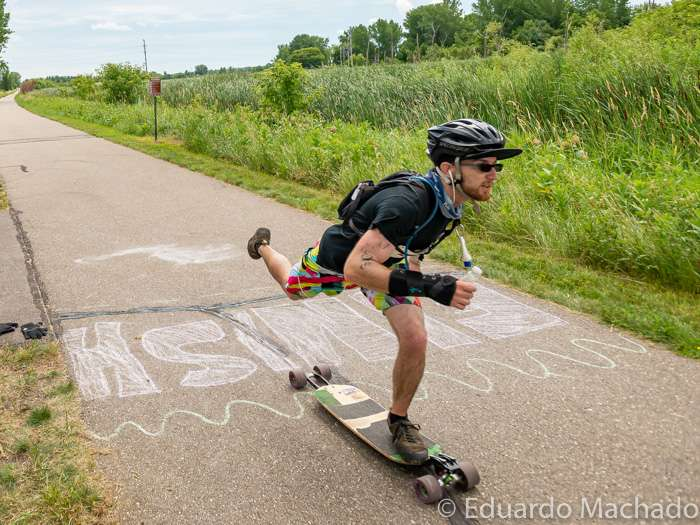A skateboarder passes the finish line on a trail