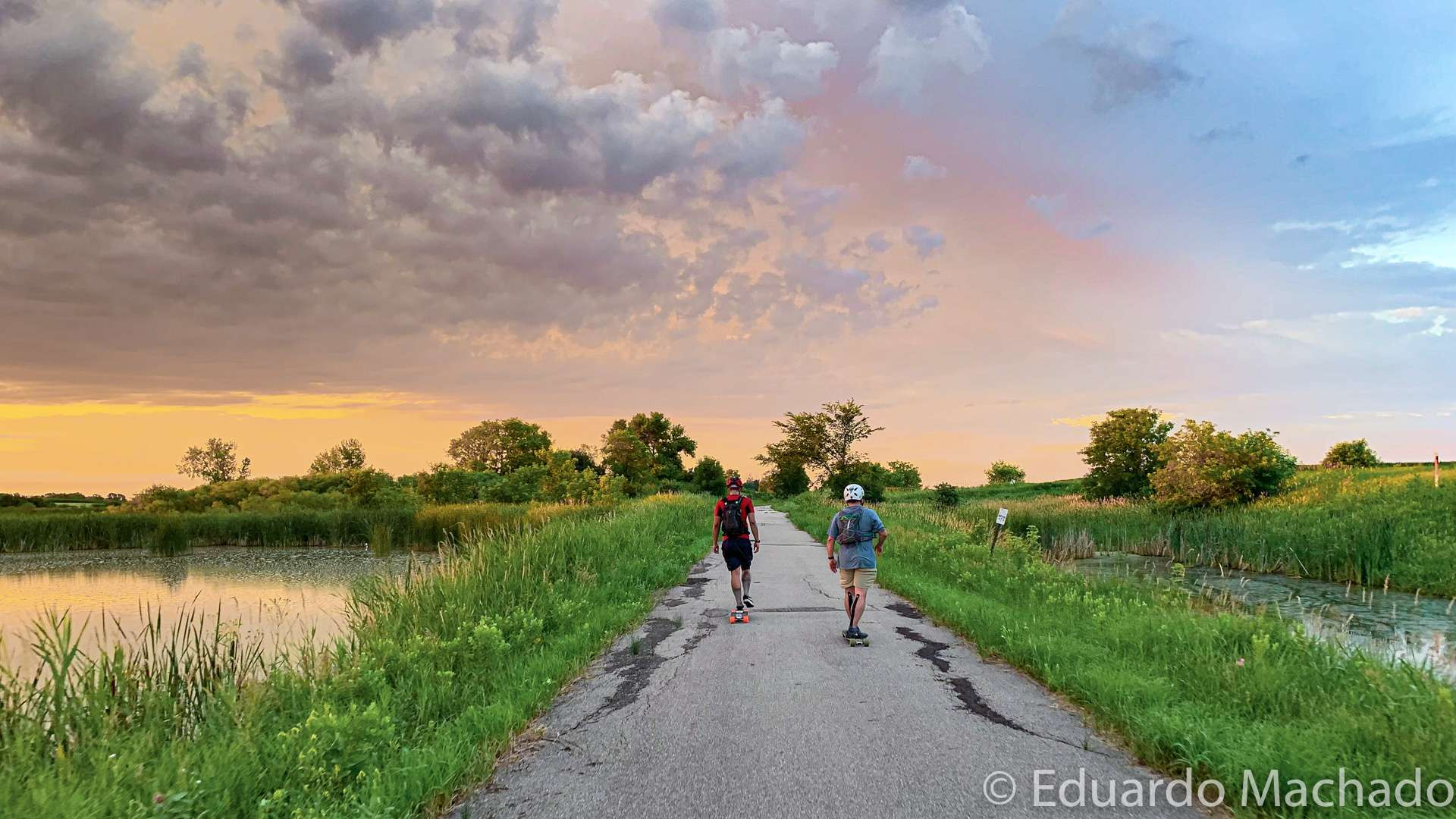 Two men roll down a trail on skateboards at sunset