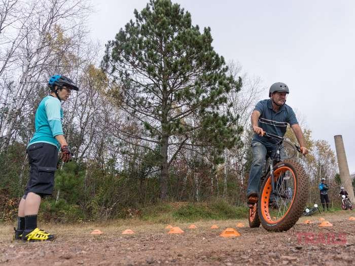 A mountain bike instructor watches a man make a turn on a mountain bike