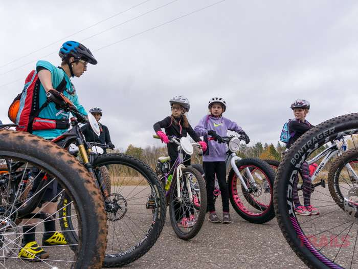 Three young girls listen to a mountain biking instructor