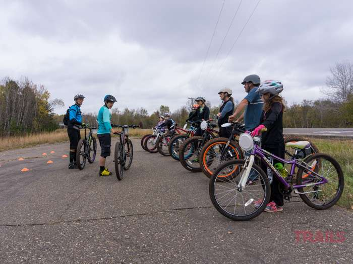 A group of mountain bikers listens to an instructor