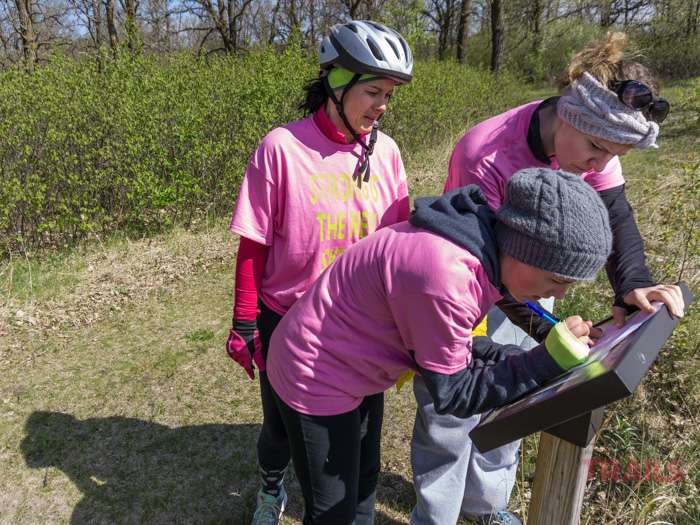 Three women stop to read an interpretive sign on a river bank