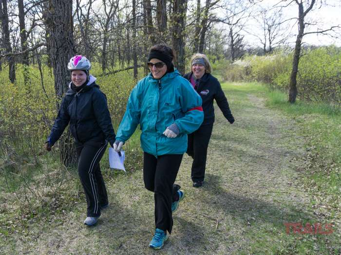 Three women walk down a trail in the spring