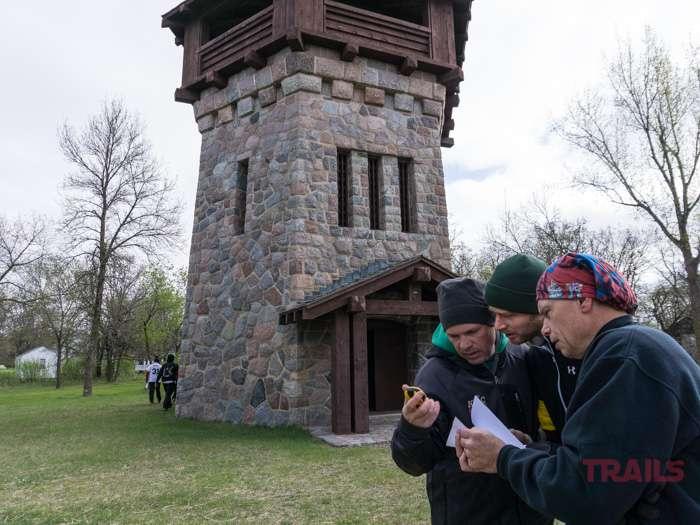 Three men consult a handheld GPS unit