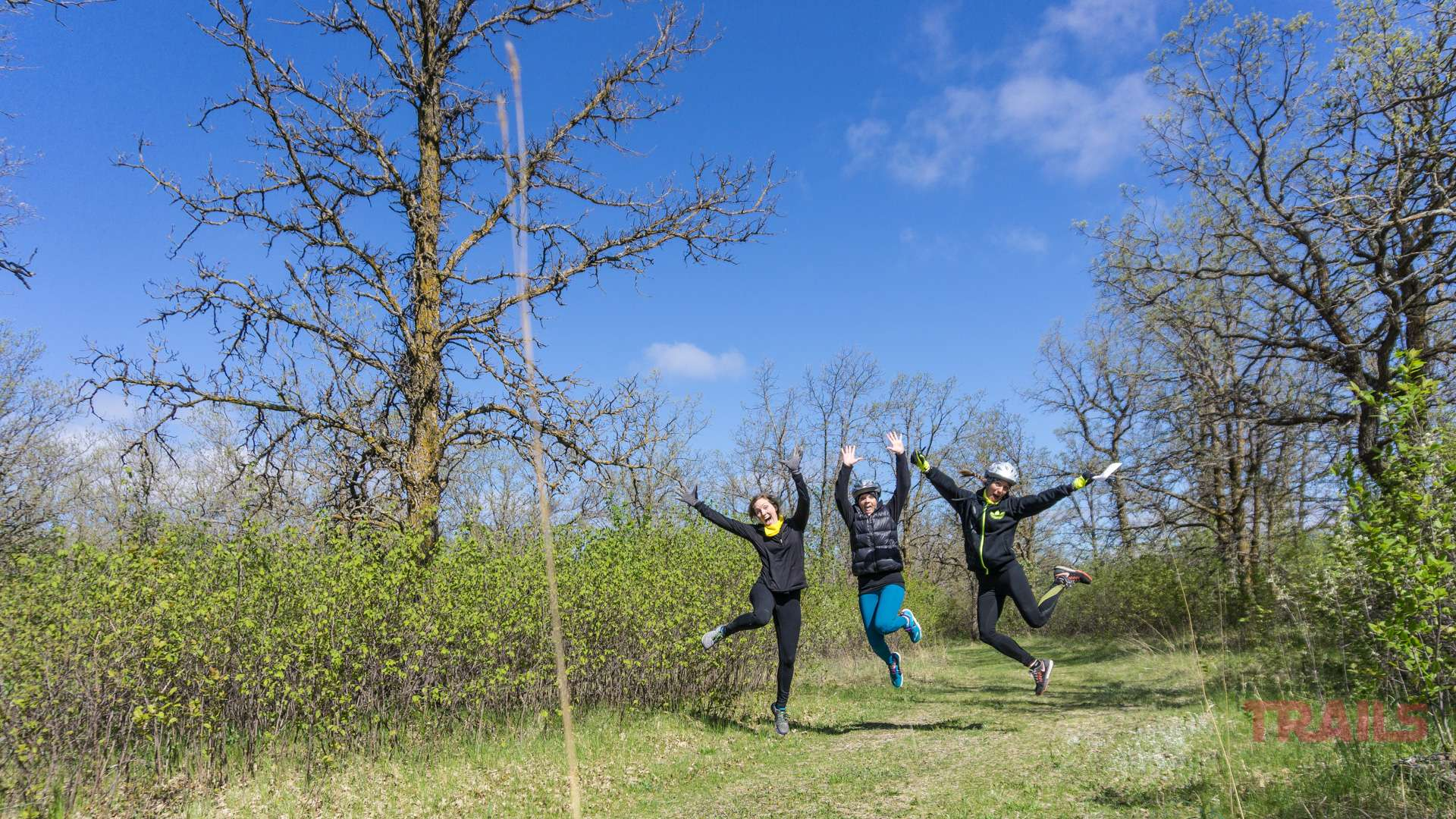 Three women jump in the air while running outdoors
