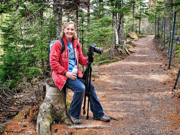 A woman sits on a tree stump holding a camera