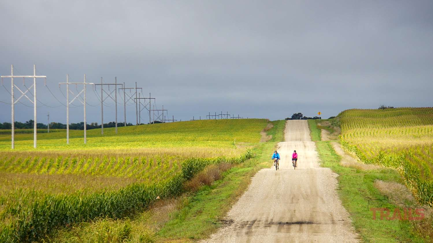 Two cyclists are biking down a steep hill on a gravel road