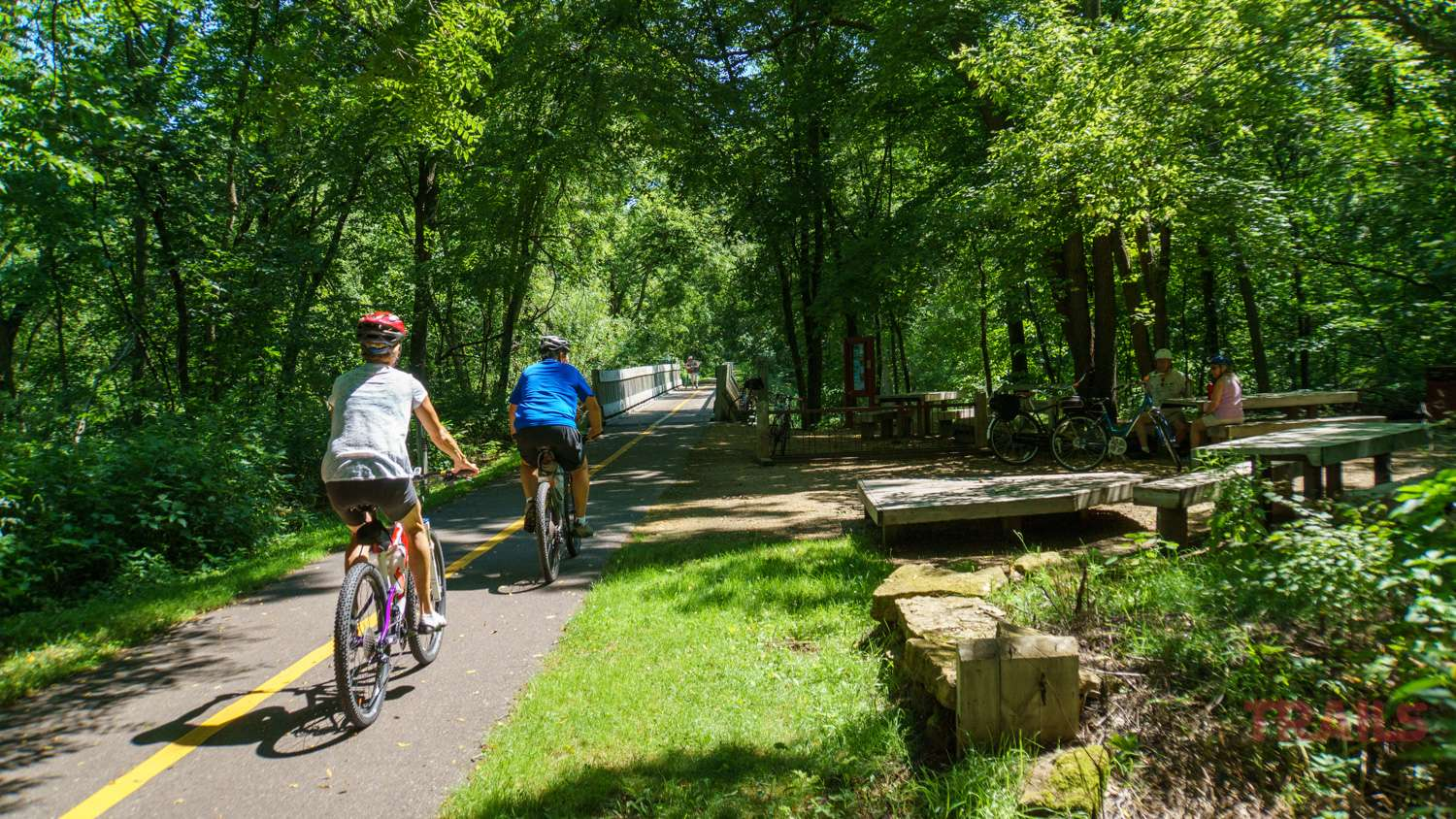 a man and a woman bike past a rest area on a trail