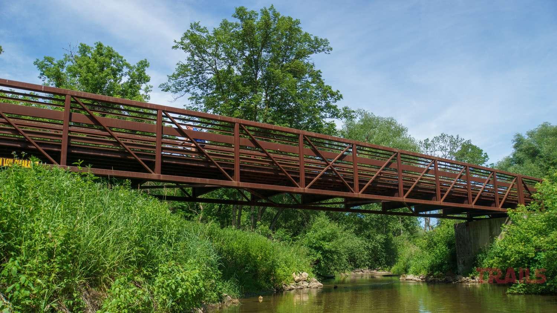 A person on a bike crosses a creek on a metal bridge