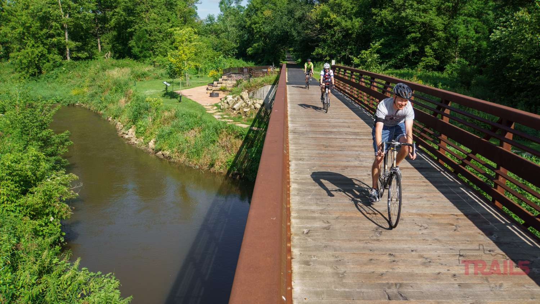 three men on bikes cross a creek on a metal bridge