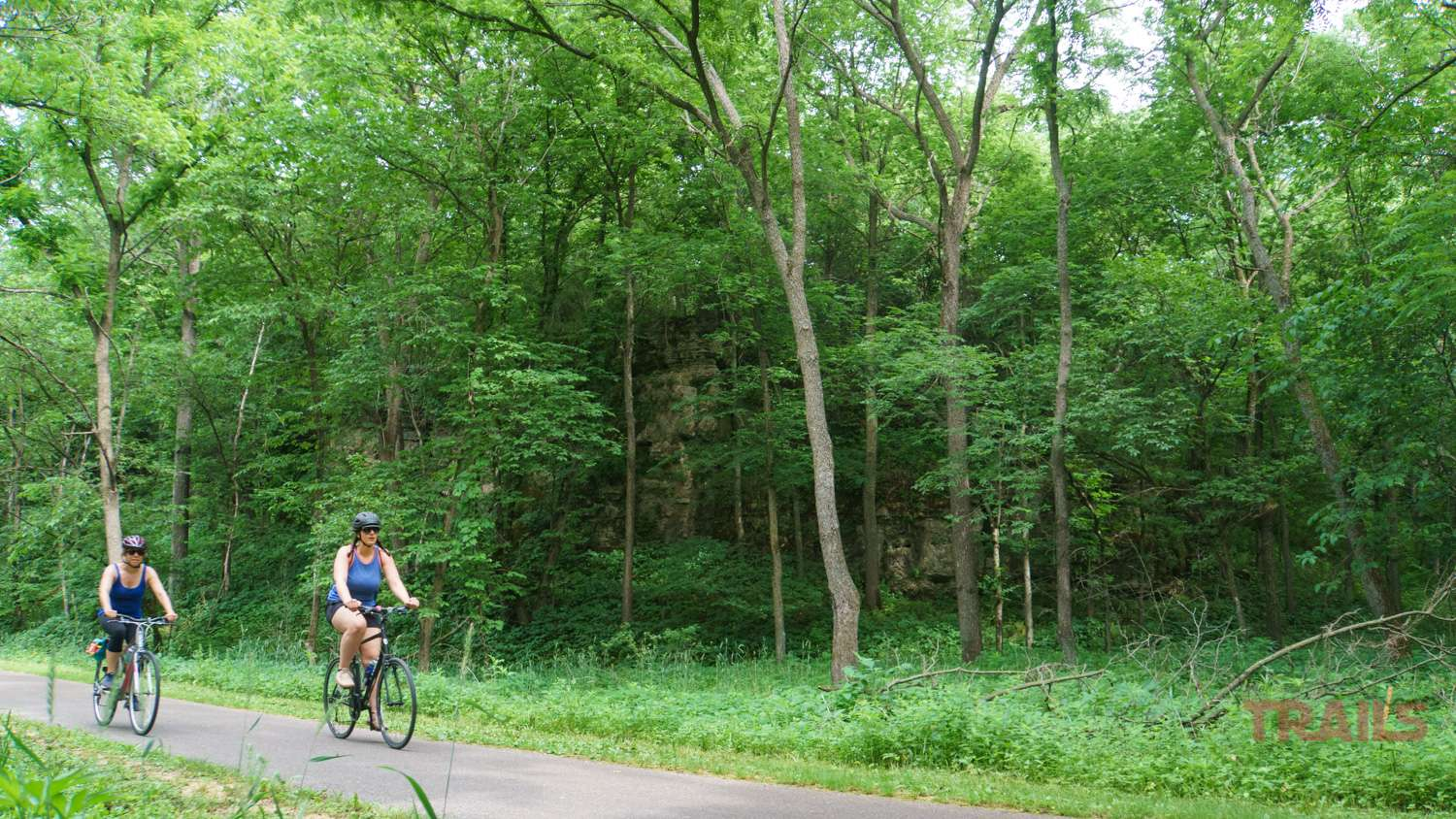 Two women bike on a trail lined with trees