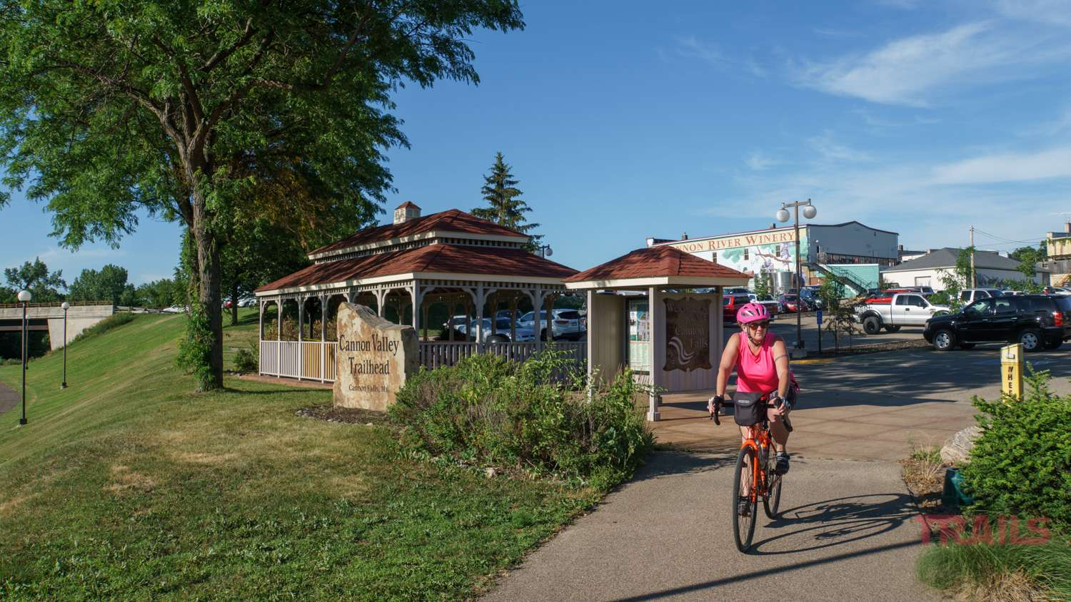A woman bikes out of a parking lot onto a paved trail