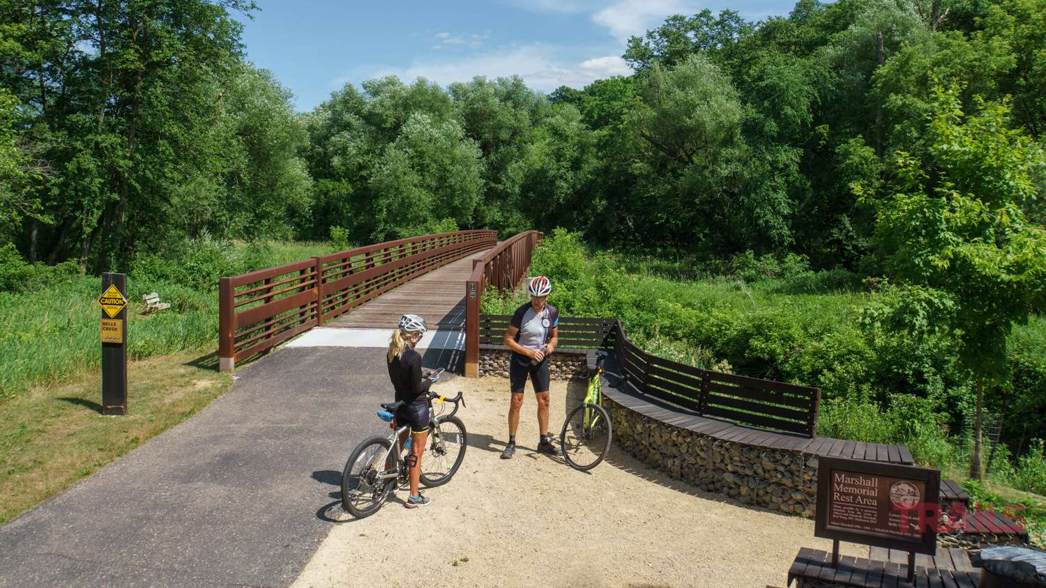 Two bicyclists are taking a break at a rest stop in an open area lined by trees along a bike trail